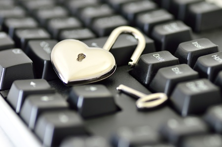 Computer security. Close-up of Heart-shaped padlock on keyboard.