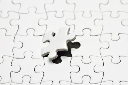 Plain white jigsaw puzzle, on Black background. Stock Photo - 13761817