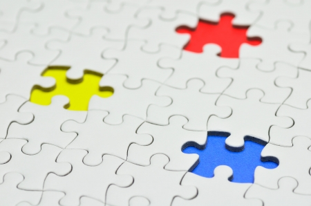 Plain white jigsaw puzzle, on Blue Red Yellow background. Stock Photo