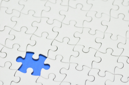 Plain white jigsaw puzzle, on Blue background.
