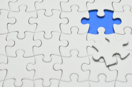 Plain white jigsaw puzzle, on Blue background. photo