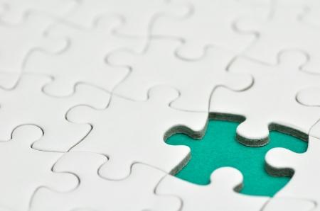 Plain white jigsaw puzzle, on Green background. Stock Photo
