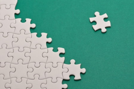 Plain white jigsaw puzzle, on Green background. Stock Photo - 13991889