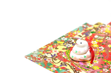 gaily: Japanese Snake figurine and gaily colored paper.