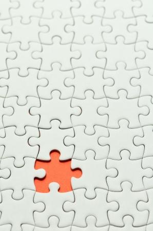 Plain white jigsaw puzzle, on orange background.  photo