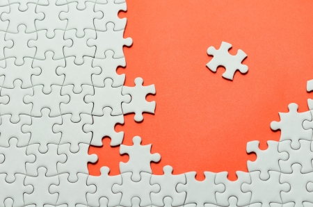 Plain white jigsaw puzzle, on orange background.  photo