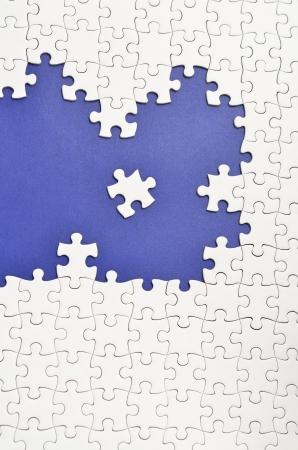 Plain white jigsaw puzzle. (Mount in dark blue) Stock Photo