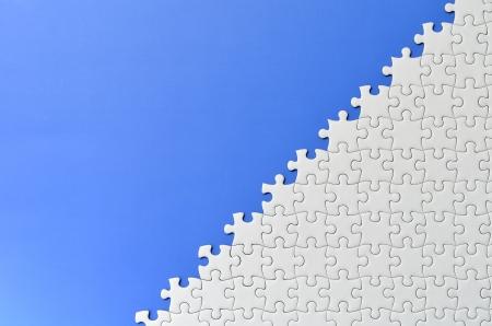 Plain white jigsaw puzzle, on Blue background.