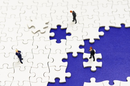 Plain white jigsaw puzzle and Businessman, on Deep Blue background. Stock Photo
