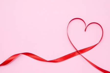 Red heart ribbon isolated on Pink background.