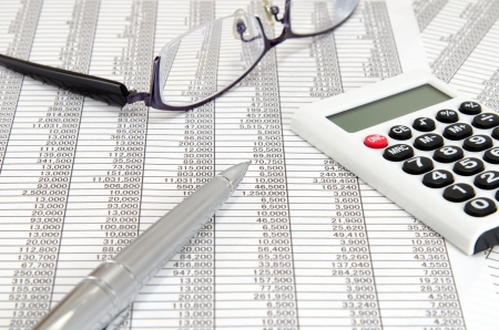 The close-up of a the calculator and ballpoint and glasses and Accounting documents.