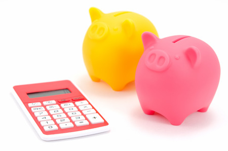 Piggy bank (Pink and Yellow) and calculator isolated on white background. photo