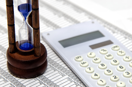 Hourglass and accounting documents and calculator photo