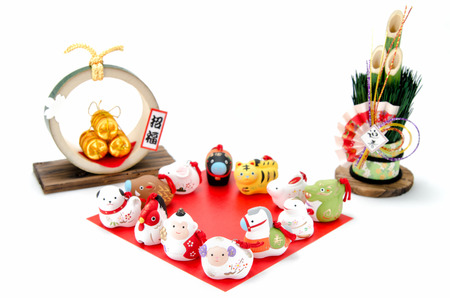 Figurines of the zodiac and New Years pine and Three golden straw rice bags. Figurines of 12 including the year of the Sheep. Imagens
