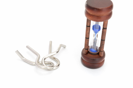 Wire puzzle (Puzzle ring)  and Hourglass on a white background.