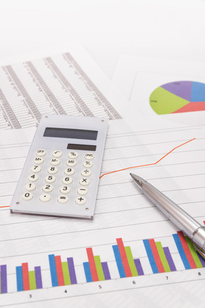 Business performance analysis. Business Graphs with calculator, pen. Stock Photo