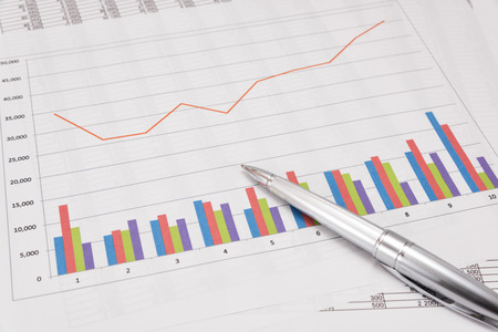 cerrando negocio: Análisis de desempeño de negocios. Gráficos de negocios y la pluma. Foto de archivo