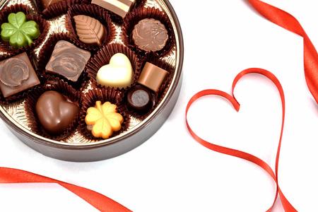Chocolade gift en rood hart lint op witte achtergrond.