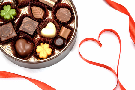 Chocolate gift and Red heart ribbon on white background.