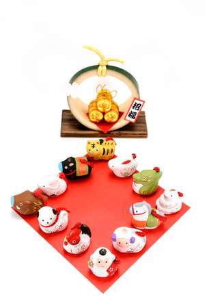 Figurines of 12 including the year of the Monkey. Figurines of the zodiac and Three golden straw rice bags. photo