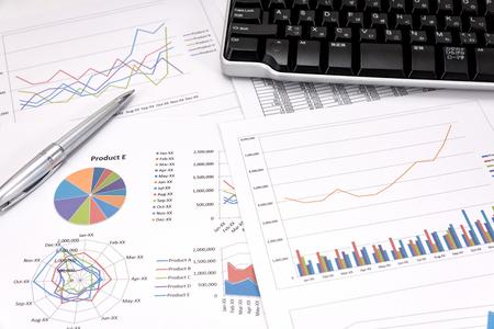 auditoría: Análisis de rendimiento empresarial. Gráficos de negocios con el teclado, pluma. Foto de archivo