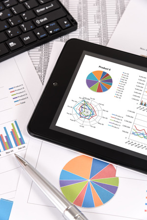 Business performance analysis. Business Graphs with tablet, pen. Stock Photo