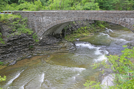 stony: Taughannock Creek flowing under stony bridge- New York Stock Photo