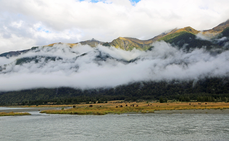 Scarfs of clouds in Haast river valley, New Zealand Stock Photo