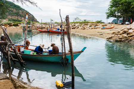 2 Fisherman are gathering and choosing mussel shell on their small fishing boat Stock Photo