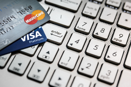 tarjeta visa: Bangkok, Thailand - August 24, 2017: Close up shot of 2 credit cards VISA and Mastercard on laptop computer with enter button focusing.