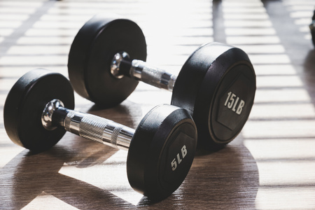Dumbbell set indoor on brown wood floor with hard shadow from large window