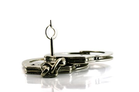 delinquent: handcuffs with key in focus, isolated on white