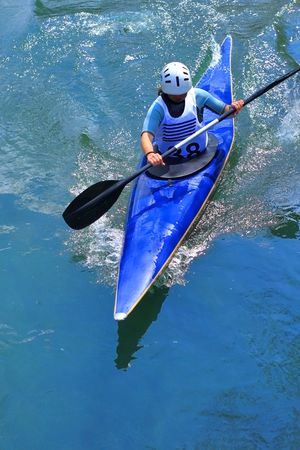 kayaker manouvring in calm blue river