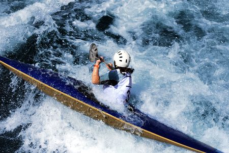 kayaker manoeuvring in calm blue river Banco de Imagens