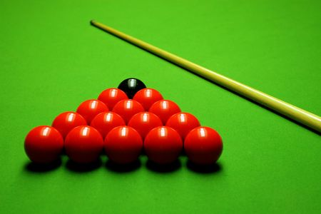 pool hall: Cue stick and snooker balls over green surface, shallow depth of field