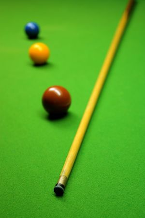 pool halls: Cue stick and snooker balls over green surface, shallow depth of field