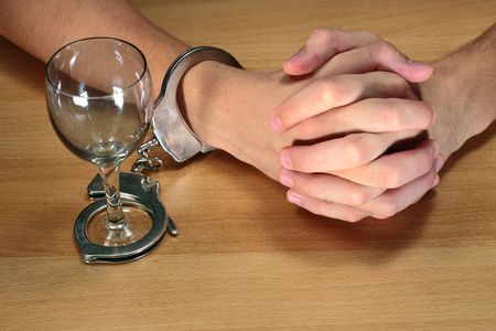 waiting convict: alcohol addiction, hands handcuffed with an empty alcohol glass