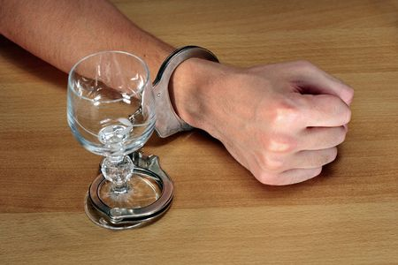 alcohol addiction, hands handcuffed with an empty alcohol glass photo
