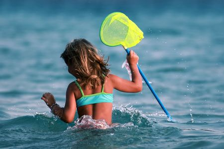netlike: young girl having fun in the water with yellow net