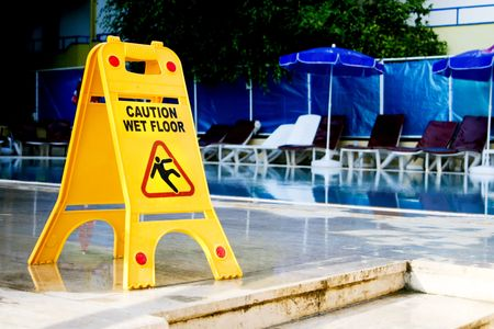 caution wet floor sign by the pool Stock Photo