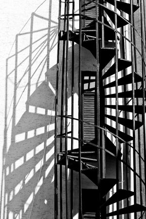 spiral stairway: old spiral fire escape stairs, black and white photo Stock Photo