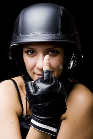 middle of the road: portrait of a beautiful girl with US Army-style motorcycle helmet, and gloves, showing middle finger