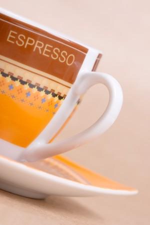 ochre: orange espresso cup on ochre background Stock Photo