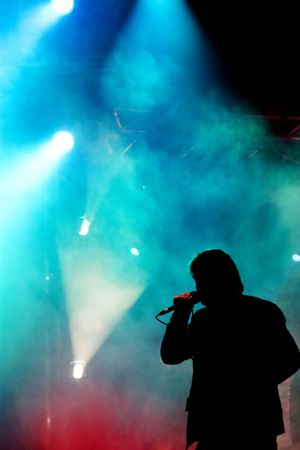 rock singer: silhouette of a singer performing on a stage Stock Photo