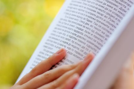 cyrillic: female hand holding a cyrillic alphabet book, outdoors Stock Photo
