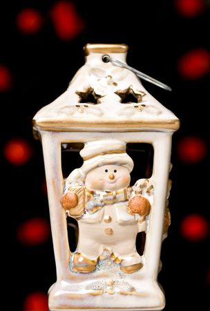 snowwhite: christmas candle holder, with defocused red light bulbs in the background