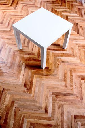 mixflooring: modern little white table on wooden floor Stock Photo
