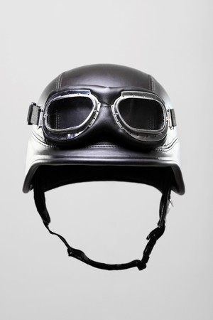 a helmet: old-style us army motorcycle helmet with goggles, on gray background