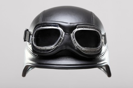 old-style us army motorcycle helmet with goggles, on gray background