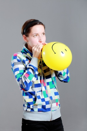 girl inflating a yellow smiley balloon, against grey background photo